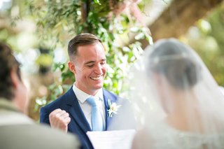 groom-in-navy-blue-suit-and-light-blue-tie-smiles-and-fist-pumps-yes-gesture-during-wedding-ceremony
