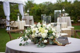 low-floral-cascading-arrangement-foliage-white-flowers-wood-votives-round-table