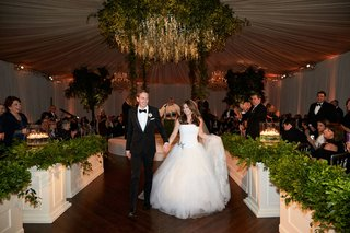 bride-in-strapless-vera-wang-wedding-dress-holding-skirt-and-groom-hand-tuxedo-wood-floor-chicago