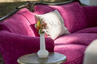 bright-pink-fuchsia-antique-sofa-wood-backing-with-side-table-white-vase-with-yellow-flowers-lounge