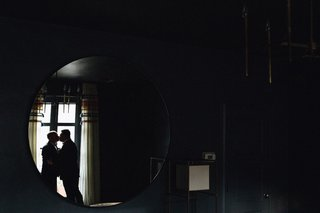 same-sex-wedding-inspiration-silhouette-of-two-grooms-kissing-reflected-in-round-mirror