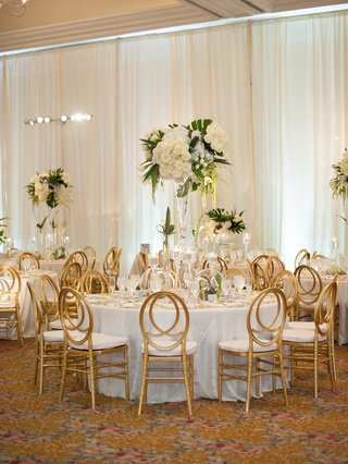 round-white-table-gold-back-oval-chairs-tall-centerpiece-white-roses-amaranthus-monstera-leaves