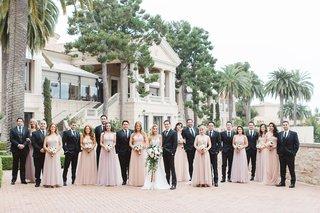 newlyweds-bridesmaids-groomsmen-scattered-pose-pelican-hill-resort-newport-california-wedding-party
