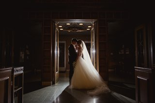 bride-in-mira-zwillinger-wedding-dress-with-mark-ingraham-overskirt-with-groom-in-tux-backlit