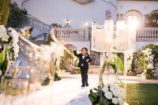 wedding-ceremony-evening-jewish-custom-ring-bearer-in-tuxedo-walking-down-white-aisle-candles-lights