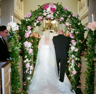 bride-and-dad-walking-through-floral-arch
