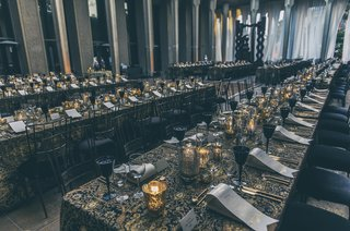 draped-tables-in-black-and-gold-linens-with-only-candlelight-for-an-intimate-dinner-reception