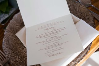 a-white-card-with-a-couples-reception-menu-in-gold-calligraphy