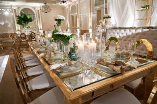 wedding-reception-gold-mirror-glass-table-gold-chairs-white-cushion-rose-greenery-centerpiece