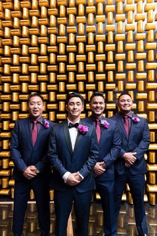 groom-in-navy-tuxedo-with-black-lapels-groomsmen-in-navy-suits-purple-shirts-fuchsia-ties