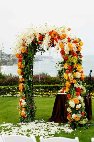 ceremony-arch-covered-in-vibrant-flowers-and-crystals
