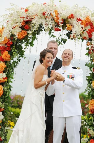 officiant-and-couple-under-floral-archway