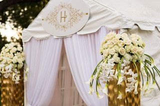 outside-of-white-wedding-reception-tent-with-embellished-gold-monogram