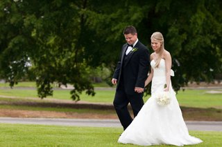 bride-in-a-strapless-fit-and-flare-wedding-gown-walks-with-groom-in-a-black-tuxedo