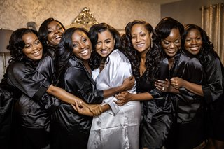 bride-in-white-satin-robe-bridesmaids-in-black-satin-robes-bride-and-bridesmaids-hug-while-getting