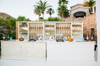 tequila-bar-at-cabo-san-lucas-wedding-reception-pink-flowers-botles-of-tequila