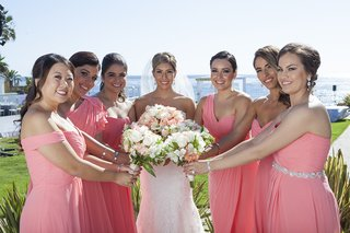 bride-in-strapless-wedding-dress-with-bridesmaids-in-different-dresses-in-coral-with-blush-bouquets
