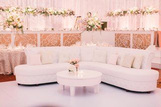 wedding-reception-lounge-furniture-white-tufted-sofa-with-light-pink-and-tan-pillows-pink-roses