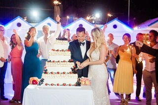 bride-groom-cutting-traditional-italian-wedding-cake-while-guests-hold-sparklers-in-the-background