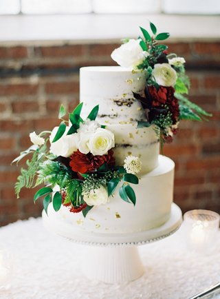 wedding-reception-brick-wall-cake-stand-white-three-layer-cake-with-greenery-white-rose-red-flower