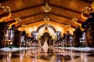 flower-petals-and-candles-along-aisle-checker-floor-at-san-diego-venue-wood-beam-ceiling