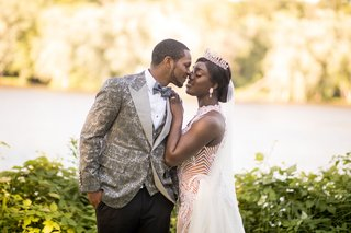groom-in-grey-patterned-tuxedo-jacket-vest-and-bow-tie-bride-in-high-neck-gown-tiara-veil-kiss