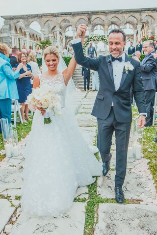bride-in-lace-a-line-isabelle-armstrong-gown-raising-arm-with-groom-after-ceremony-at-bahamas