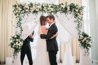 bride-in-j-mendel-wedding-dress-groom-in-suitsupply-suit-couple-hugging-in-front-of-arch