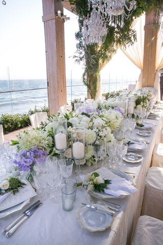 wedding-reception-long-table-with-candles-pillar-with-white-flower-arrangements-chandeliers-overhead