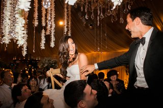 bride-and-groom-look-at-each-other-during-hora-dance-wedding-reception-flower-chandelier