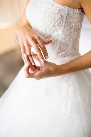 bride-in-monique-lhuillier-ball-gown-puts-on-heirloom-diamond-ring-from-grandmother