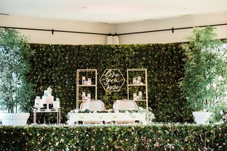wedding-reception-hedge-wall-gold-bookcase-bar-cart-with-cakes-vintage-sweetheart-table