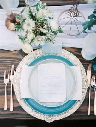 white-and-blue-tablescape-with-blue-plates-and-white-chargers-on-a-wooden-table-with-green-florals