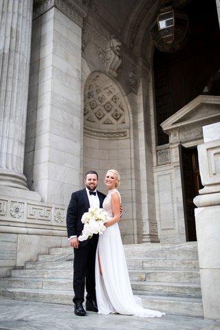 bride-in-julie-vino-wedding-dress-front-high-slit-sleeveless-groom-in-tuxedo-in-front-of-new-york