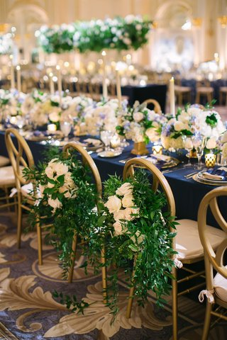 wedding-reception-head-table-navy-blue-linens-gold-chairs-greenery-and-white-flowers-on-bride-groom