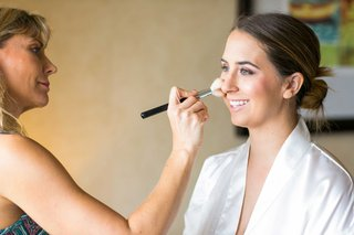 bride-in-white-robe-has-makeup-applied-on-her-wedding-day