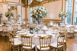 wedding-reception-gold-ballroom-blue-white-vases-greenery-white-flowers-gold-chairs-charger-plates