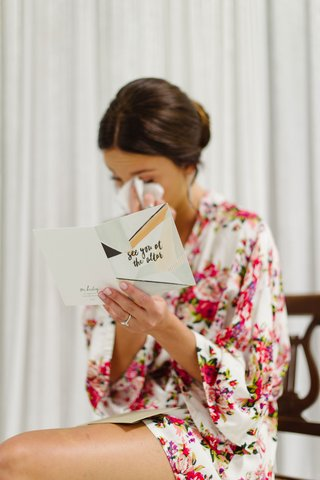 bride-in-flower-print-robe-crying-while-reading-card-see-you-at-the-altar-from-groom-getting-ready