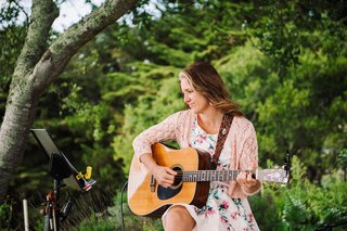 woman-in-sun-dress-playing-guitar-at-outdoor-ceremony