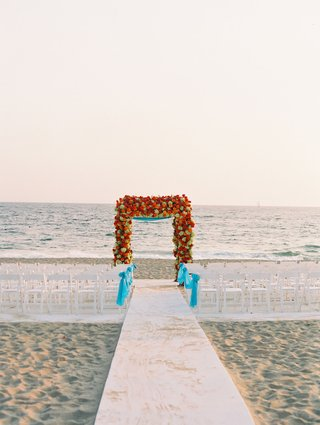 beach-wedding-ceremony-in-malibu-blue-turquoise-ribbon-and-flower-arch-of-red-and-yellow-blooms
