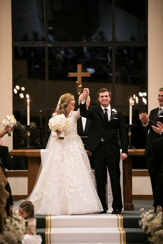 bride-in-isabelle-armstrong-lace-gown-groom-in-tuxedo-arms-raised-in-celebration