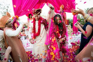 bride-and-groom-recessional-at-indian-wedding-with-vibrant-magenta-and-yellow-flower-petal-toss