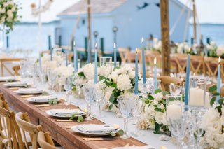 blue-tapered-candles-interspersed-amongst-collection-of-ivory-florals