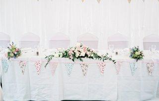 white-head-table-diy-details-low-floral-arrangements-handmade-flags-ivory-blush-flowers