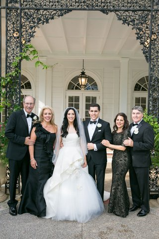 wedding-portrait-bride-and-groom-with-parents-mothers-in-black-dresses-one-shoulder-three-quarter