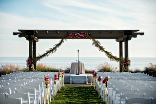 rustic-wood-arbor-at-wedding-ceremony-with-garland-and-pink-flowers