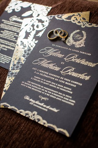 wedding-invitation-with-wedding-rings-and-band-on-top-black-stationery-gold-lettering-and-monogram