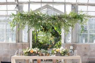 greenhouse-wedding-venue-reclaimed-wood-sweetheart-table-greenery-overhead-low-centerpiece-rustic