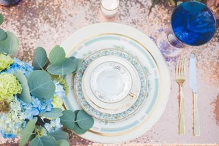 pale-blue-and-gold-china-rose-gold-linens-gold-flatware-blue-glassware-colored