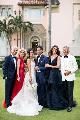 bride-and-groom-with-parents-in-formal-wedding-attire-jewish-wedding-red-dress-dark-midnight-gown